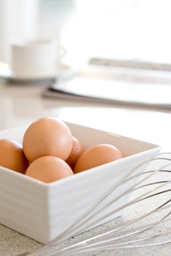 eggs in a white bowl with whisk