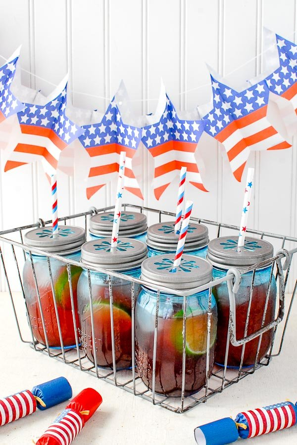 Six blue jars filled with Firecracker Punch recipe for Fourth of July