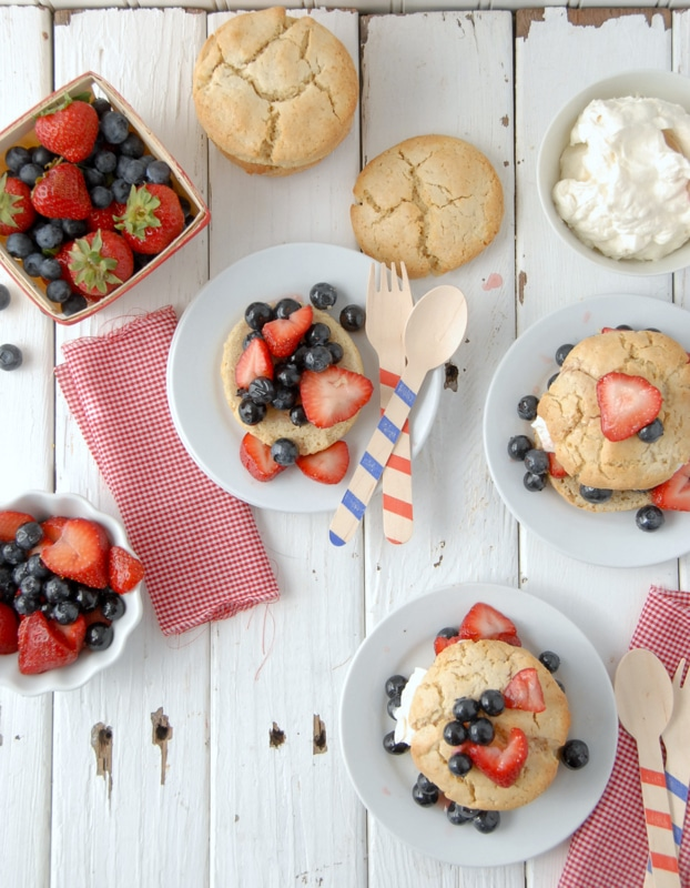 Multiple servings of All American Berry Buttermilk Shortcakes with fresh strawberries and blueberries, freshly whipped cream on small white plates with red and blue striped wooden spoons and forks - BoulderLocavore.com