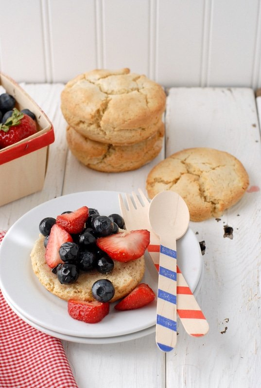 Freshly baked All American Berry Buttermilk Shortcakes with fresh berries, red and white gingham napkin, red striped wooden spoon and blue striped wooden fork - BoulderLocavore.com