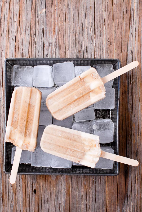 Root Beer Float Popsicles on a bed of square ice in a vintage metal pan on a wood surface BoulderLocavore.com