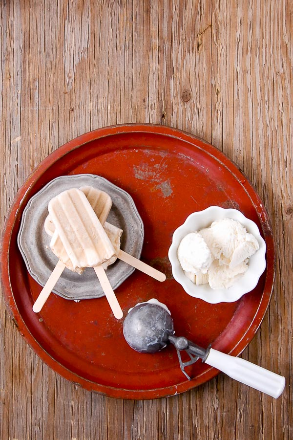 Three Root Beer Float Popsicles with wooden sticks, on a pewter plate with white bowl of vanilla ice cream, vintage ice cream scooper on a distressed red metal tray BoulderLocavore.com