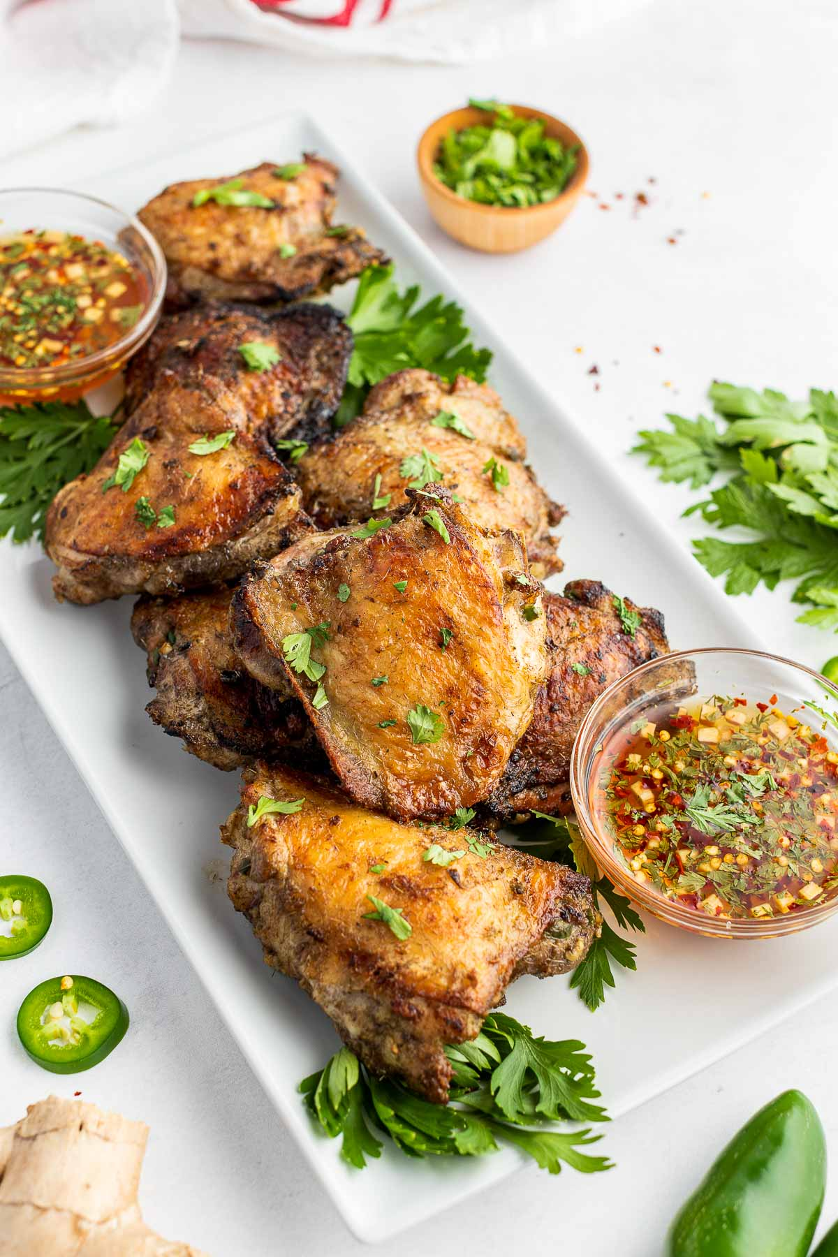 grilled chicken thighs with dipping sauce on platter