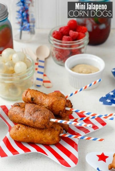 Mini Jalapeno Corn Dogs iwth patriotic sticks on a striped star plate with food in background