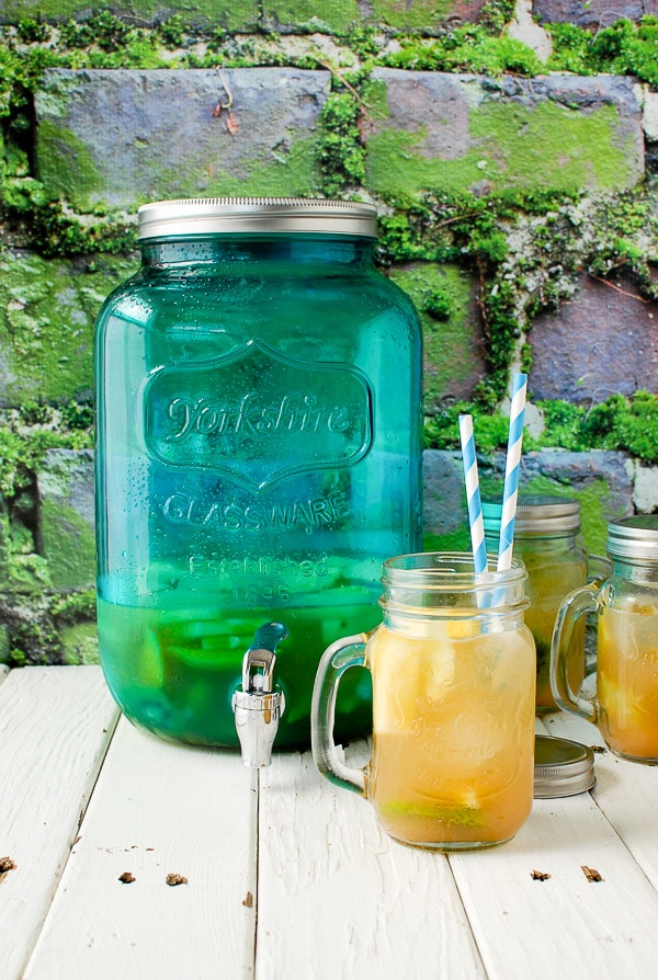 Cold, refreshing Tropical Fruit Sangria in Mason jar mugs with blue striped paper straws, a blue glass infusing jar with spigot on vintage distressed white painted fence boards BoulderLocavore.com