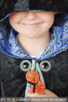 child in a cloak holding a halloween sucker
