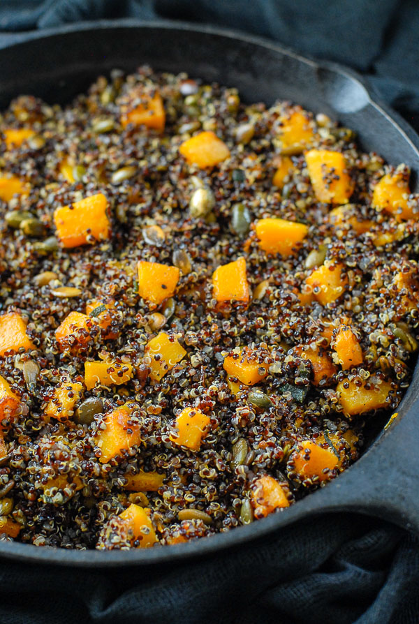 cast iron skillet of black quinoa in sage brown butter sauce with butternut squash
