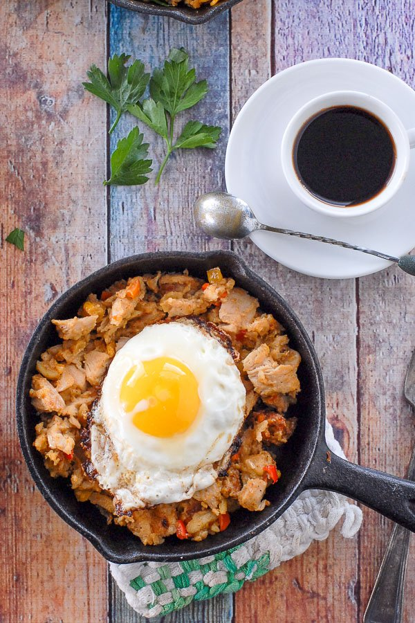 mini skillet of turkey hash with a fried egg on top and coffee cup