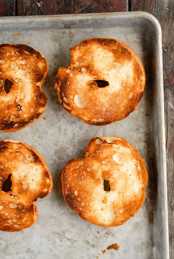 toasted bagel halves on baking sheet