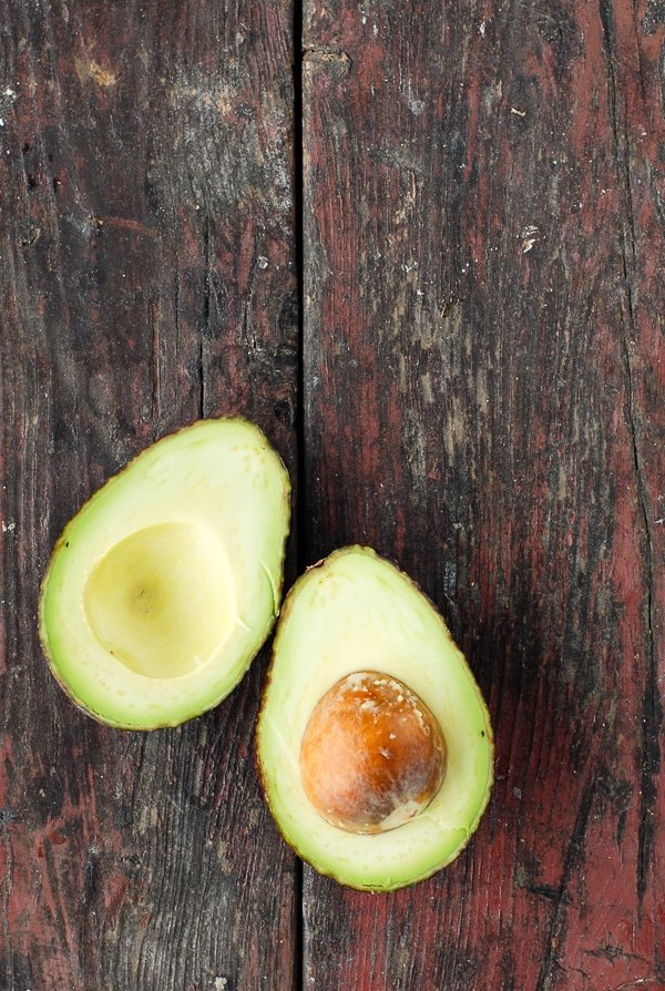 sliced avocado pm a distressed wood surface