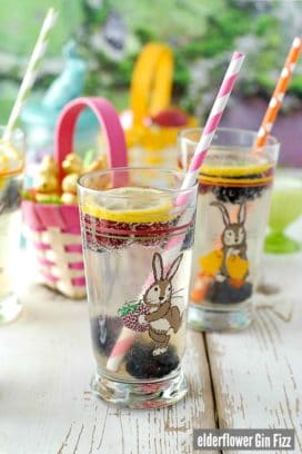 Elderflower Gin Fizz cocktails in easter glasses with colorful straws and frozen berries