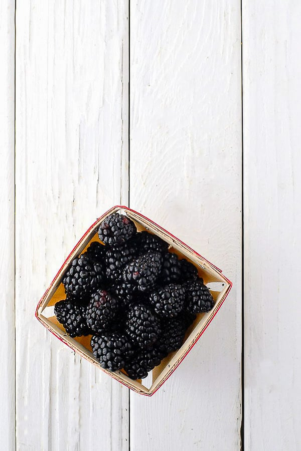 Freshly picked blackberries in a wooden berry carton on antique white painted wood BoulderLocavore.com