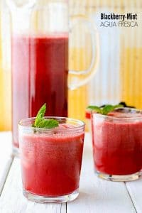 Fresh, light Blackberry Mint Agua Fresca with fresh mint sprigs on vintage white wood with yellow background
