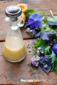 Homemade Meyer Lemon Salad Dressing with fresh greens and edible flowers