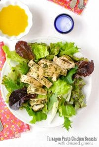 Quick, juicy chicken breasts topped with homemade tarragon pesto served on dressed mixed green salad on a white plate