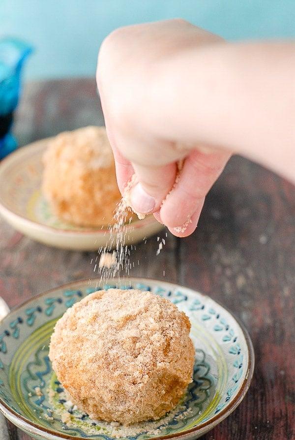 sprinkling cinnamon sugar on fried ice cream balls