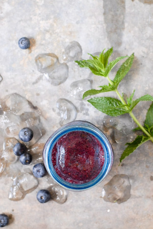 Healthy fresh Blueberry Mint Daiquiri on distressed metal surface with fresh blueberries, mint sprig and ice BoulderLocavore.com