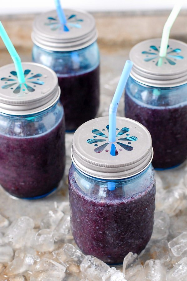Fresh, frozen Blueberry Mint Daiquiri cocktails in blue pint Mason jars with metal flower lids and straws on a bed of ice BoulderLocavore.com