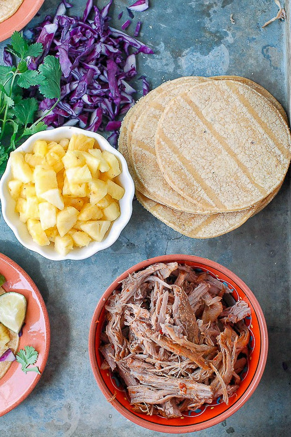 Tacos Al Pastor ingredients: slow cooker pork, pineapple chunks, corn tortillas and red cabbage