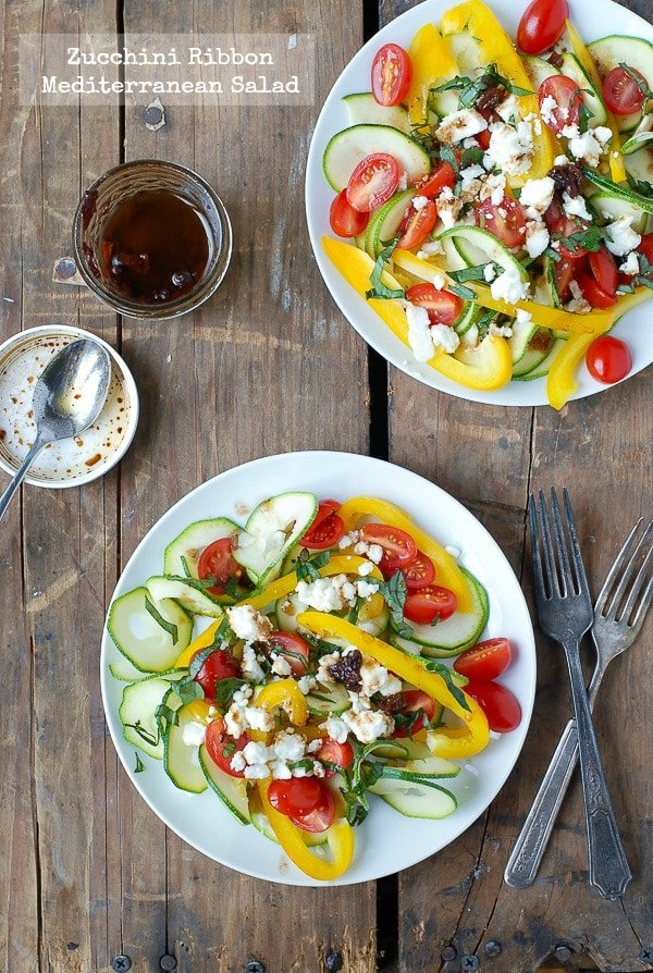 2 white plates of Zucchini Ribbon Mediterranean Salad on a weathered wood background
