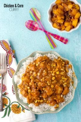 Easy to prepare Chicken and Corn Curry on white rice on a blue ruffled Anthropologie plate with Indian napkin, Sabre spoons and peach chutney BoulderLocavore.com