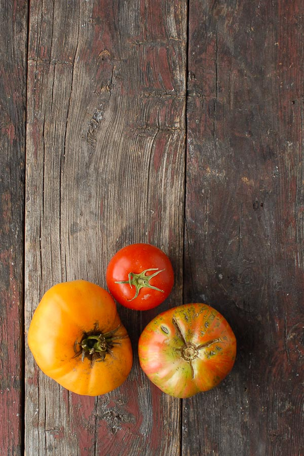 Ripe colorful heirloom tomatoes on distress wood plank Boulderlocavore.com
