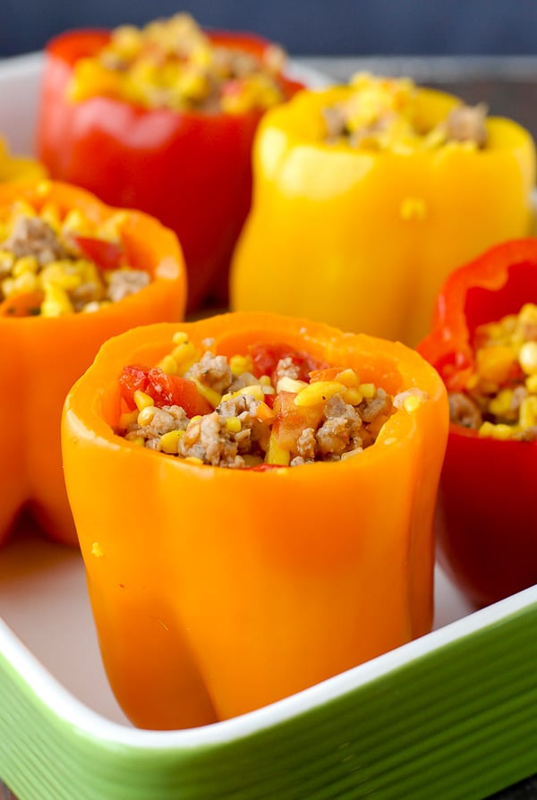 Colorful orange, red and yellow Sausage and Orzo Stuffed Sweet Peppers with sensational seasonal ingredients and gluten-free option BoulderLocavore.com
