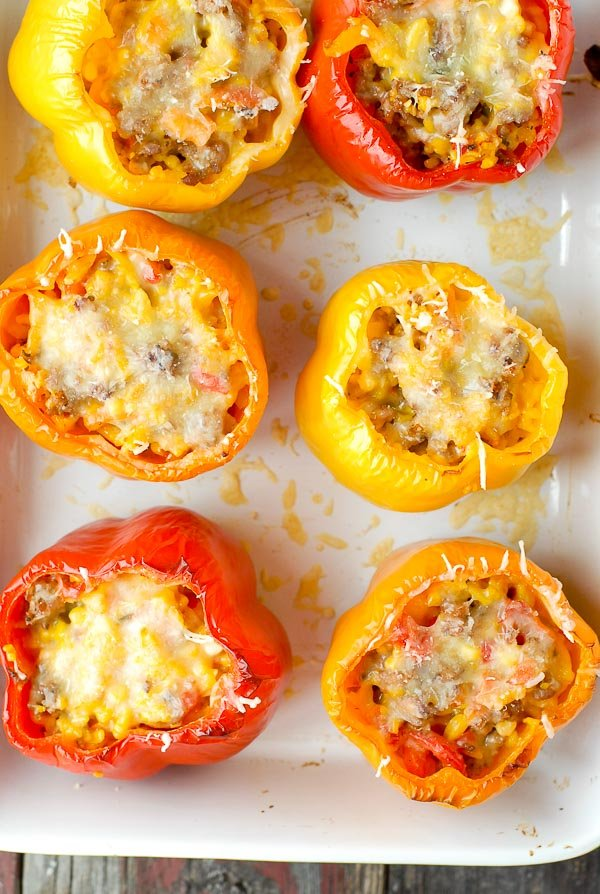 Red, yellow and orange Sausage and Orzo Stuffed Sweet Peppers with melted Monterey Jack cheese in a white enamel baking dish BoulderLocavore.com
