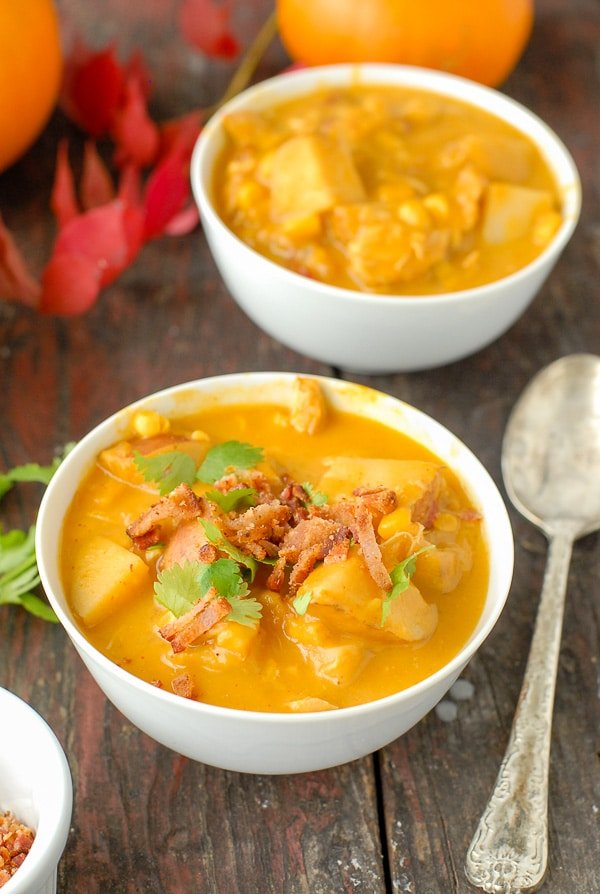 white bowls of slow cooker spicy pumpkin chicken corn chowder with bacon