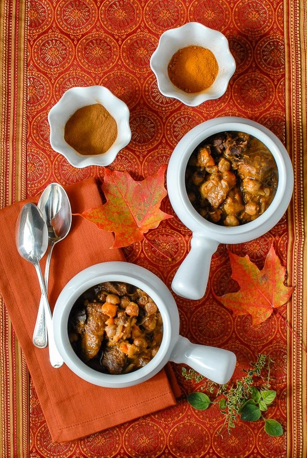white bowls of Sweet & Spicy Slow Cooker Beef Stew iwth spices and fall leaves