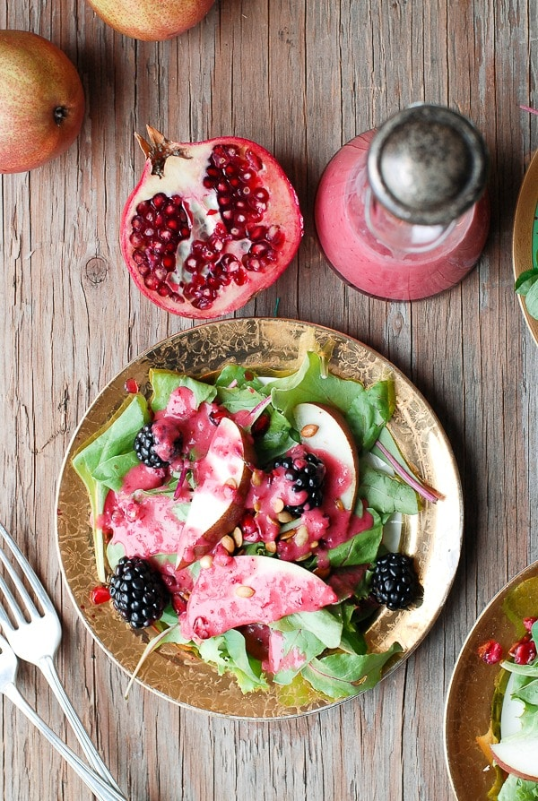Winter Salad with pears and blackberries with Warm Cranberry Honey Dressing on a vintage gold rimmed salad plate