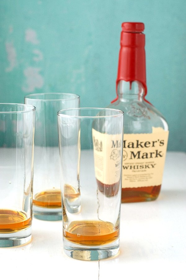 three Collins glasses with bourbon in them and Marker's Mark bottle