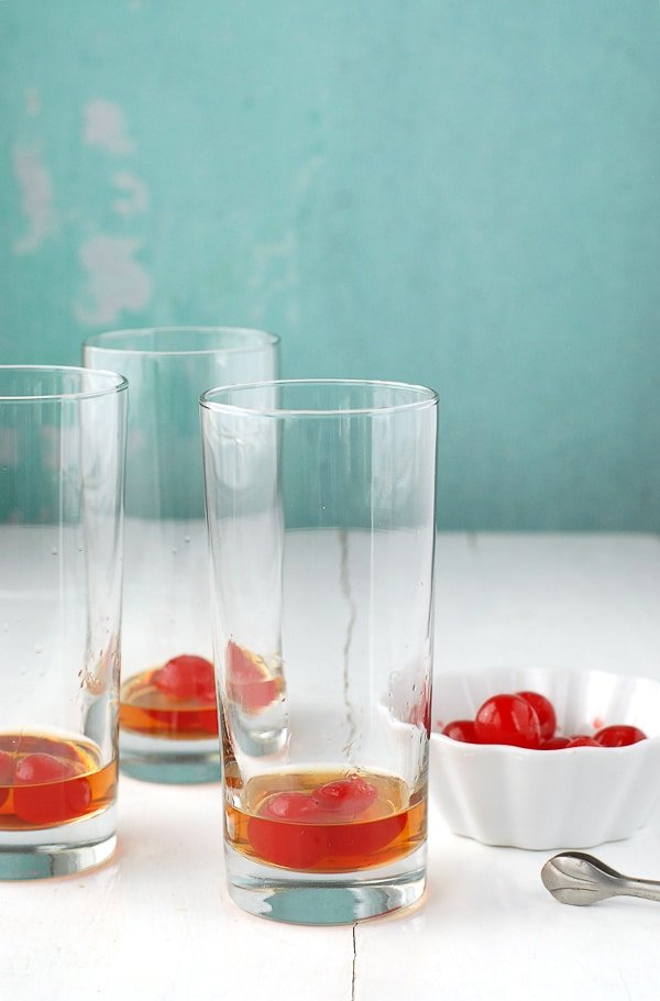 three Collins glasses with bourbon and maraschino cherries with a white bowl of cherries