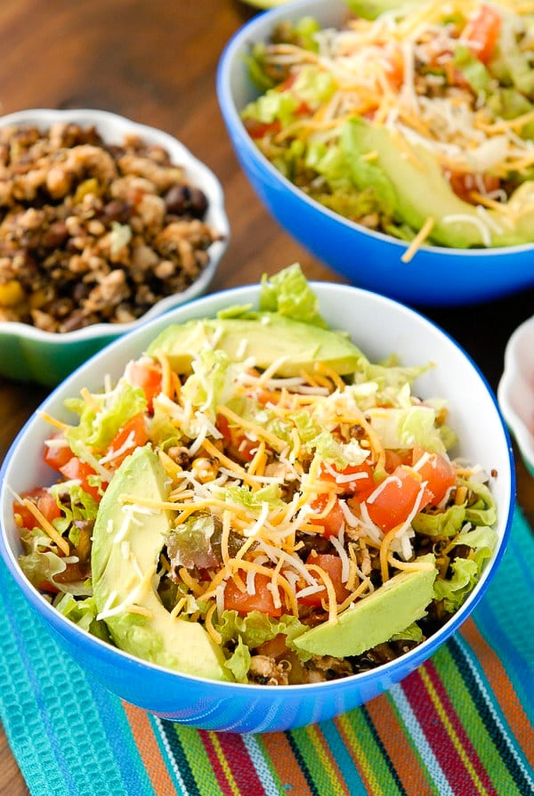 Light and Lean Turkey Black Bean Quinoa Burrito Bowls with shredded lettuce, grated cheese, avocado slices on a striped Mexican napkin BoulderLocavore.com