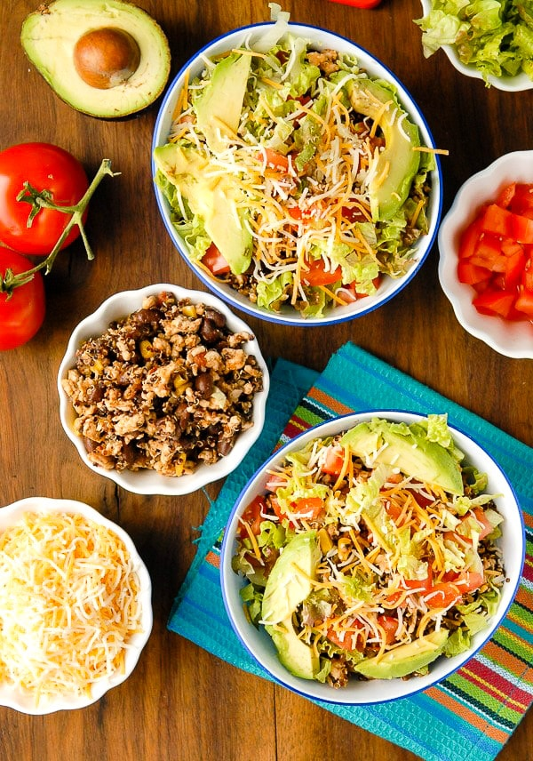 Gluten-free lean Turkey Black Bean Quinoa Burrito Bowls with grated Mexican cheese, fresh chopped tomatoes, avocado and Mexican napkin BoulderLocavore.com