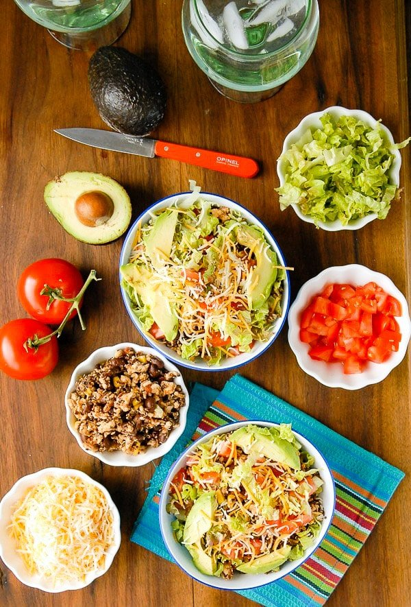 Lean Turkey Black Bean Quinoa Burrito Bowls with shredded lettuce, chopped fresh tomatoes, orange French Opinel knife and blue striped mexican napkin BoulderLocavore.com