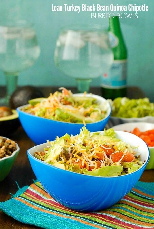 Lean Turkey Black Bean Quinoa Burrito Bowls topped with Mexican Cheese in blue bowls