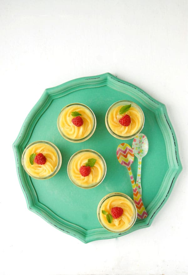 Mini Mascarpone Key Lime Curd Cheesecakes in Jars on a teal tray with colorful Sabre French spoons
