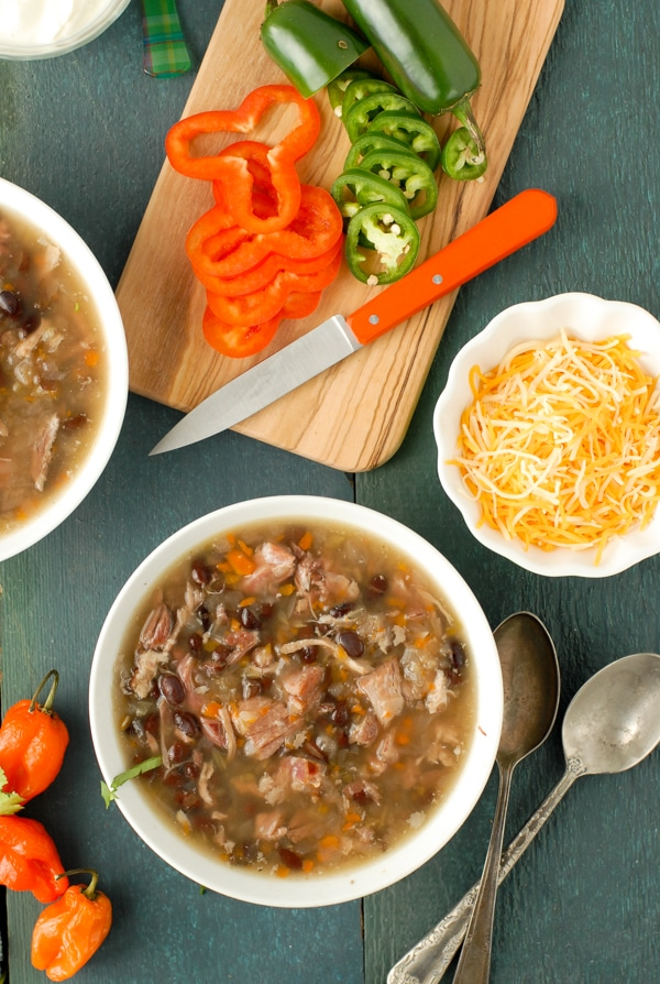 Bowl of chunky slow cooker black bean and hambone soup with cumin, sliced jalapeno peppers on cutting board and bowl of grated cheese