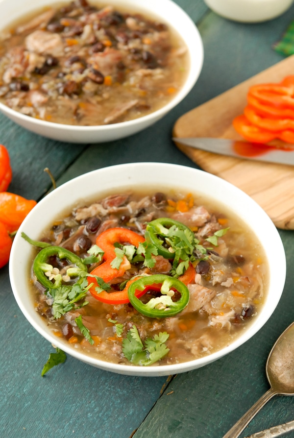 Hot bowl of slow cooker black bean and hambone soup with cumin topped with sliced jalapenos, red pepper and torn cilantro