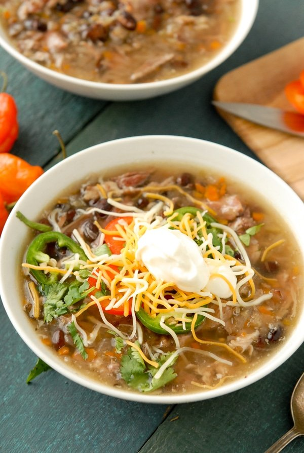 Fully loaded bowl of slow cooker black bean and hambone soup with cumin topped with grated cheddar cheese and sour cream