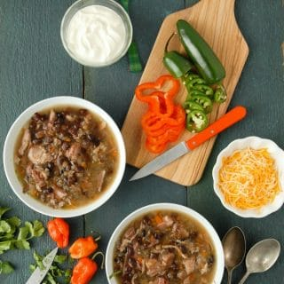 Two white bowls of slow cooker black bean and hambone soup with cumin with freshly cut peppers