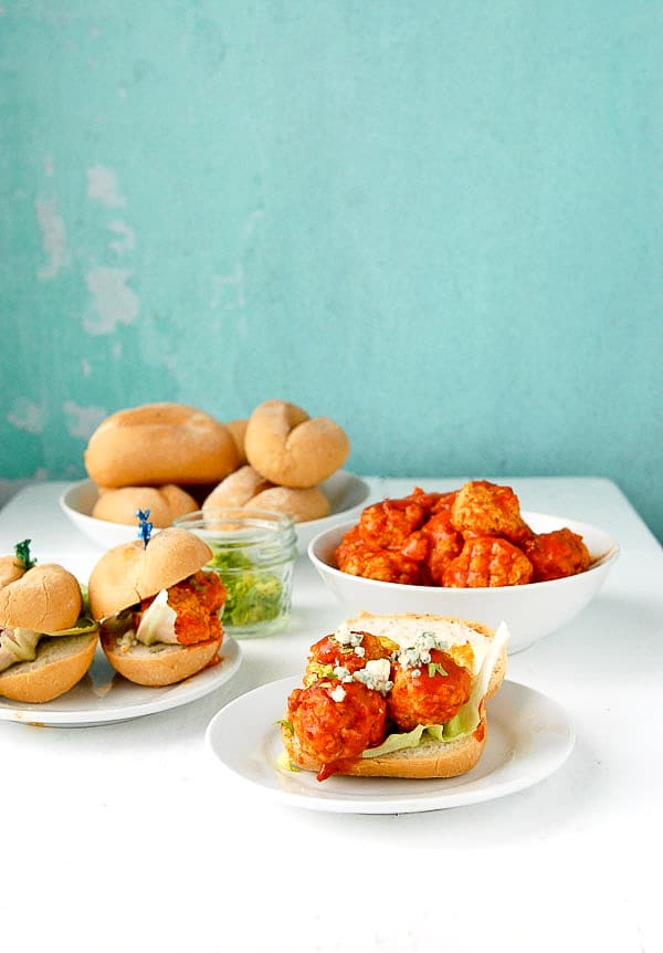 white tabletop with gluten-free slow cooker buffalo chicken meatball mini sandwiches and a bowl of meatballs