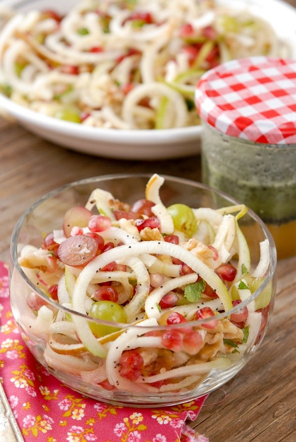 Glass bowl of Spiralized Apple and Pears Pomegranate Slaw with Honey-Poppy Seed Dressing