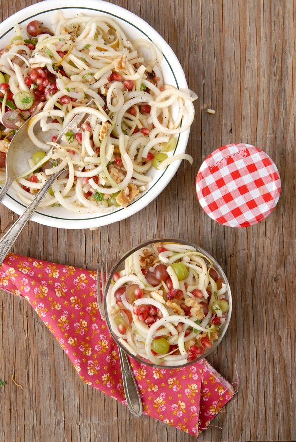 A serving bowl and individual serving of Spiralized Apple and Pears Pomegranate Slaw with Honey-Poppy Seed Dressing