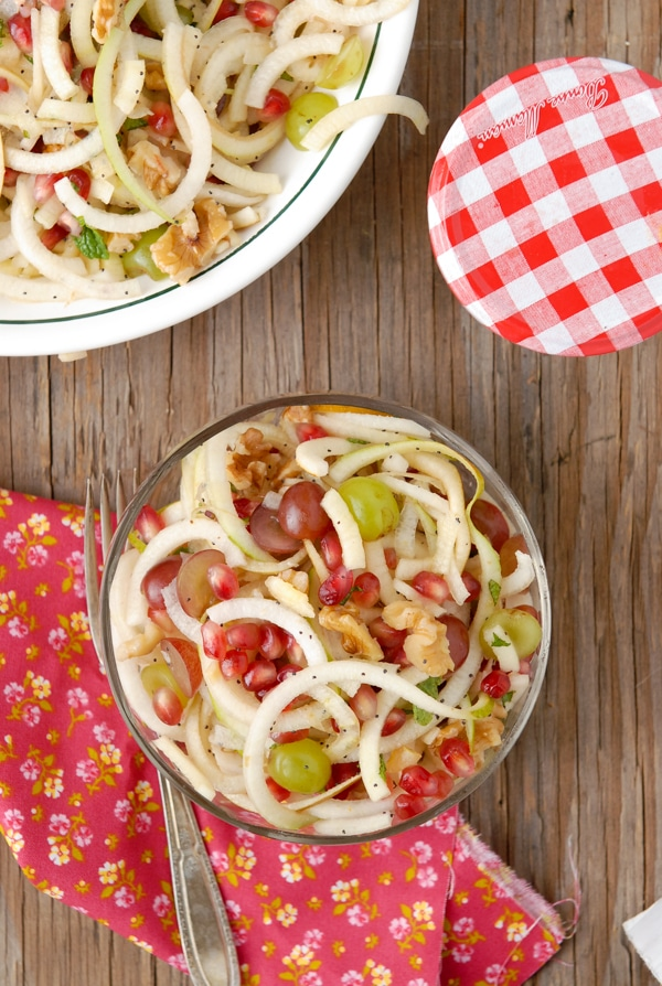 Glass bowl of spiralized Apple and Pears Pomegranate Slaw with Honey-Poppy Seed Dressing from above with flower napkin