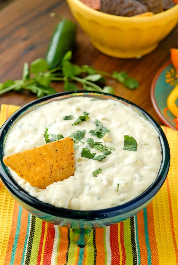 Slow Cooker White Queso Green Chile Dip {Queso Blanco} with torn cilantro on top and corn chip in the dip