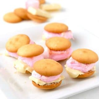 Oven S'mores made with Vanilla Wafers, Rose Marshmallows, and melted White Chocolate on a white plate.