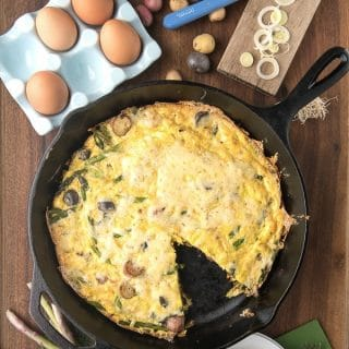Simple and seasonal Asparagus Leek New Potato Frittata topped with melted Havarti Dill cheese in a cast iron skillet