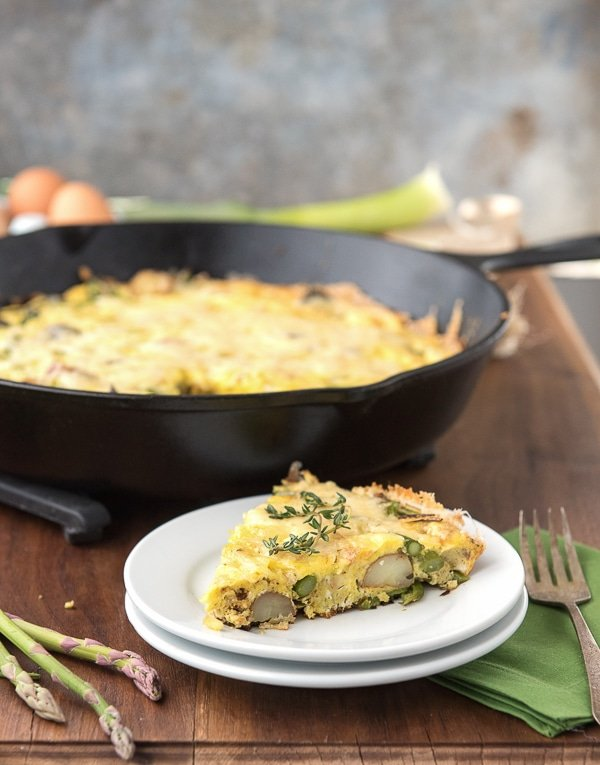 Easy Asparagus Leek New Potato Frittata slice topped with thyme on a white plate